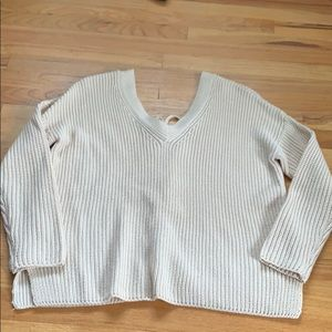 Beige sweater with a braided tie down the back.